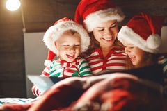 Merry Christmas! family mother reads to children a book before bed in bed royalty free stock photos