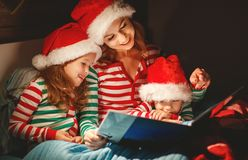 Merry Christmas! family mother reads to children book before bed stock photos