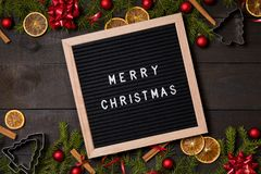 Merry Christmas letter board on dark rustic wood background wit royalty free stock images