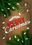 Merry Christmas. Fir-tree branch with a bright garland on a wooden board. Xmas and New Year greeting card. Stock Photos