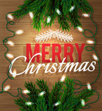 Merry Christmas. Fir-tree branch with a bright garland on a wooden board. Xmas and New Year greeting card. Royalty Free Stock Images