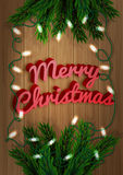 Merry Christmas. Fir-tree branch with a bright garland on a wooden board. Xmas and New Year greeting card. Royalty Free Stock Photography