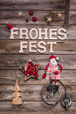Merry Christmas in german letters with santa in red and wooden d Royalty Free Stock Photo