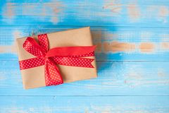 Merry Christmas gift box or Valentine Present on blue wooden background royalty free stock photos