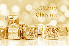 Merry Christmas gifts in shiny golden paper Royalty Free Stock Photos