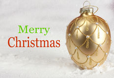Merry Christmas Gold. Merry Christmas and a bulb in gold. Snow in the background stock photos