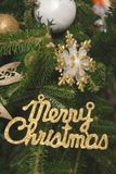 Merry christmas gold gleaming inscription and baubles. Merry Christmas gold gleaming inscription and glitter gold ornaments on a fir tree. Green New Year or stock photo