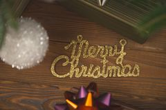 Merry christmas gold gleaming inscription on a rustic wooden background. Merry Christmas gold gleaming inscription under a Christmas-tree, gift boxes and baubles stock image