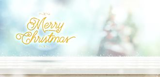 Merry Christmas gold glitter on white wooden table with abstract. Muted blur christmas tree and snow fall background with bokeh light,Holiday backdrop,Mock up royalty free stock photo