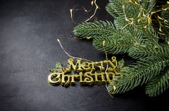 Merry Christmas inscription, fir and lights on chalk blackboard. Merry Christmas gold inscription, fir branhes and newyear lights on black background. Copy space royalty free stock photo