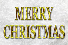 Merry Christmas Gold Letters in Snow. Merry Christmas greeting message in gold letters against a snow background Royalty Free Stock Image