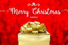 Merry Christmas with Golden Present box at red bokeh light backg Royalty Free Stock Images
