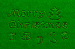 Merry Christmas golden text and attributes on green velvet surface. Embossed extruded text inscription, tree, bell, gift boxes embroider in gold over the silk Stock Images