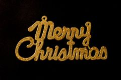 Merry Christmas golden text on a black background. Merry Christmas shiny golden text on a black background stock photography