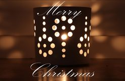 Merry christmas greeting with candle in cup with a holes which divide the light into many beautiful shades.  royalty free stock photography
