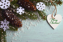 Merry Christmas greeting card.Decorative snowflakes,fir cones,heart and snowy fir tree branch on light blue background Stock Photos