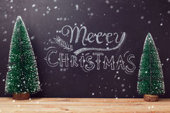 Merry Christmas greeting card design with chalkboard lettering and Christmas trees on wooden table Royalty Free Stock Photo