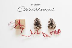 Merry Christmas greeting card. Gift box with red ribbon and pine cones on white background with congratulation text. Flat lay, top view, minimal style stock image