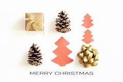Merry Christmas greeting card. Gift box with ribbon, cones and toy paper christmas tree on white background with congratulation te. Merry Christmas greeting card stock images