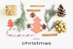 Merry Christmas greeting card. Gift box, ribbon, fir branches, cones, star anise, cinnamon, candy cane and paper christmas tree on. White background with royalty free stock photo