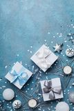Merry christmas greeting card. Gift boxes and holiday decoration on blue table top view. Flat lay. Royalty Free Stock Images