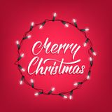 Merry Christmas. Greeting card with Merry Christmas calligraphy and shiny Christmas lights garland. Festive background Royalty Free Stock Images