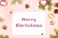 Merry Christmas greeting card with paper, fir tree branches, presents, golden decorations on pink. Top view vector illustration