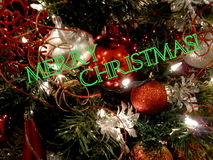 Merry Christmas greeting. Merry Christmas in green block text graphics against ornaments on Christmas tree Stock Photography