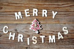 Merry Christmas greeting message with tree on wooden background Royalty Free Stock Image