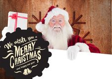 Merry christmas greetings against santa claus holding gift and placard. On wooden background royalty free stock photography