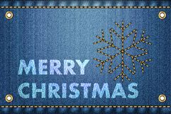 Merry Christmas greetings on blue jeans background. Stock Photos