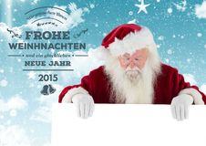 Merry christmas greetings with santa claus holding placard. Against digitally generated background stock images