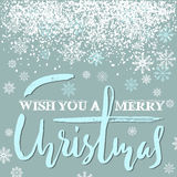 Merry Christmas grunge lettering design on blue background with white snow. Holiday lettering card. Stock Photography