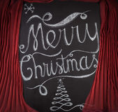 Merry Christmas hand drawn lettering design framed by red curtai Stock Images