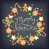 Merry Christmas Hand Drawn Lettering. Wreath of sweets, biscuit, cookie, lollipops, candies, candy cane, gingerbread Man. On a black table. For web or printing royalty free illustration