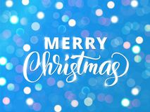 Merry Christmas text. Holiday greetings quote. White and blue sparkling glowing lights. Background with bokeh effect. Stock Images