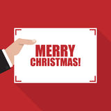Merry Christmas. Hand with sheet of paper with long shadow Stock Photo