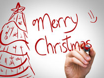 Merry Christmas Hand writing with red marker on transparent wipe board Royalty Free Stock Photos
