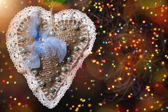 Merry Christmas heart with feather. Merry Christmas handmade sackcloth toy with blue feather. blurred background with garland, sparking, glowing and snow. Happy Stock Photography