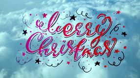 Merry Christmas handwritten calligraphic inscription on a sky blue texture. backdrop.  Stock Images