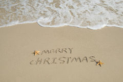 Merry Christmas handwritten in sand on beach Stock Photo