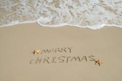 Merry Christmas handwritten in sand on beach Stock Photo