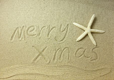 Merry Christmas handwritten in sand Stock Images
