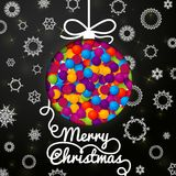 Merry Christmas handwritten swirl lettering. Greeting card on black paper with snowflakes, and cut through paper in shape of christmas ball made from bundle of Stock Photography