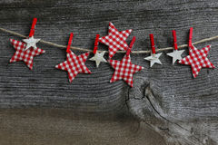 Merry Christmas Hanging Decoration Gingham And Birch Stars With. Christmas handmade decoration Birch and gingham fabric stars and red clips over rustic Elm wood Royalty Free Stock Photos