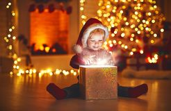 Merry Christmas! happy baby boy with magic gift at home. Merry Christmas!happy baby boy with magic gift at home near Christmas tree and fireplace royalty free stock image