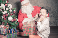Merry Christmas! Happy boy and Santa Claus with gift box Royalty Free Stock Photos