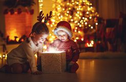 Merry Christmas! happy children with magic gift at home. Merry Christmas!happy children with magic gift at home near Christmas tree and fireplace royalty free stock photography
