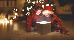 Merry Christmas! happy children with magic gift at home stock images