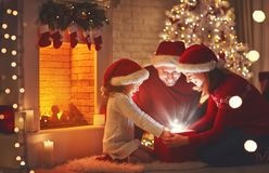 Merry Christmas! happy family mother father and child with magic. Gift near tree Stock Photography